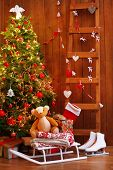 Decorated Christmas tree, ladder and sledge on wooden wall background