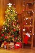 Decorated Christmas tree and ladder on wooden wall background