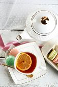 Colorful macaroons with cup of tea on color wooden table, on light background