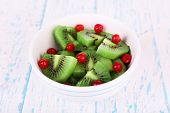 Bowl of slices kiwi with currants on color wooden background