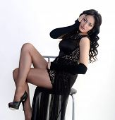 Female model in evening dress is sitting