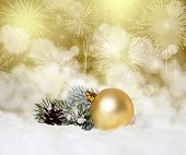 Christmas balls and fir branch in snow on bokeh background
