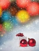 Red christmas balls and gift box on bokeh background