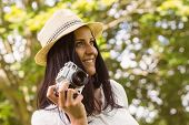 Smiling brunette in straw hat holding retro camera in the park