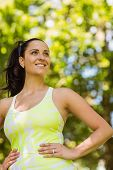 Smiling brunette in sportswear with her hands on hips in the park