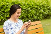 Cheerful brunette sitting on bench texting in the park