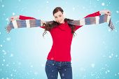 Cheerful brunette holding scarf and spread her arms against blue vignette