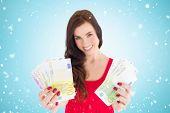 Cheerful brunette showing her cash money against blue vignette