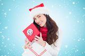 Smiling brunette holding christmas gifts against blue vignette