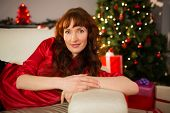 Beautiful redhead lying on the couch at christmas at home in the living room