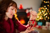Cheerful redhead holding red bauble at home in the living room
