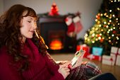 Calm redhead text messaging at christmas at home in the living room