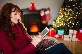 Redhead using digital tablet at christmas at home in the living room