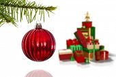 Red christmas decoration hanging from branch against green red and gold christmas gifts
