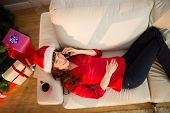 Redhead lying on the couch phoning at christmas at home in the living room