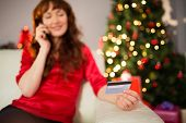 Smiling redhead phoning and holding credit card at home in the living room
