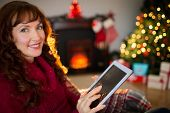 Cheerful redhead using tablet at christmas at home in the living room