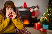 Cheerful redhead drinking hot drink at christmas at home in the living room