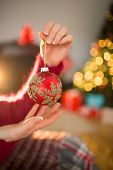 Woman in jumper holding red bauble at christmas at home in the living room