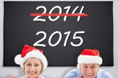 Festive couple showing poster against black chalkboard