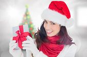 Excited brunette in santa hat showing gift against blurry christmas tree in room
