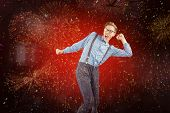Geeky hipster dancing to vinyl against colourful fireworks exploding on black background