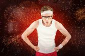 Geeky hipster posing in sportswear against colourful fireworks exploding on black background