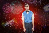 Geeky hipster pulling a silly face against colourful fireworks exploding on black background