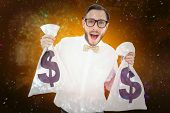 Geeky businessman holding money bags against colourful fireworks exploding on black background