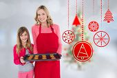 Mother and daughter with baking tray against blurry christmas tree in room