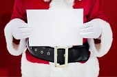 Mid section of santa claus holding page against red snowflake background