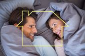 Couple having fun wrapped in their blanket against house outline