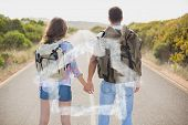 Hiking couple standing on countryside road against house outline in clouds