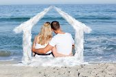 Affectionate couple sitting on the sand at the beach against house outline in clouds