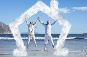 Happy couple jumping up barefoot on the beach against house outline in clouds