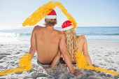 Rear view of couple sitting on beach against house outline