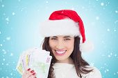 Happy brunette holding her cash against blue vignette