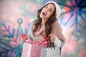 Happy brunette opening shopping bag against blurred snowflake design