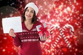 Brunette holding gift and sale sign against blurred christmas background