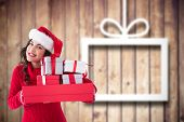 Festive brunette holding pile of gifts against blurred christmas decorations on wood