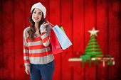 Beauty brunette posing with shopping bags against blurred christmas background