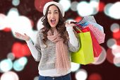 Excited brunette with shopping bags against blurry lights