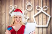Festive blonde shopping online with tablet against blurred christmas decorations on wood