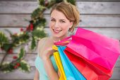 Portrait of cute young woman with shopping bags against blurred holly on wood