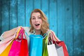 Overwhelmed young woman with shopping bags against blurred snowflakes on planks