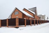 Snow Covered Red Brick House With Metal Fence
