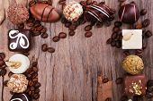 Frame of different chocolates with coffee beans on wooden textured background