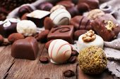 Different chocolates with coffee beans on grey fabric on wooden background
