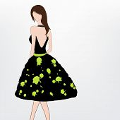 Young modern girl wearing a stylish black backless dress with green print.