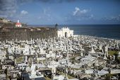 SAN JUAN, PUERTO RICO-MARCH 6, 2011: Overview of the Cementerio de Santa Maria Magdalena de Pazzis cemetery in San Juan, Puerto Rico with the ancient Spanish fort in the background